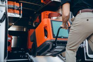 technician loading water damage restoration equipment into van